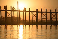 People walking on elevated wooden walkway at sunset - MINF12427