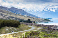 RV driving near mountains and lake in remote landscape - MINF12490
