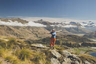 Woman standing with outstretched arms on mountain top, Roys Peak, Lake Wanaka, New Zealand - IHF00130