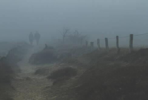 Couple walking in fog - IHF00136