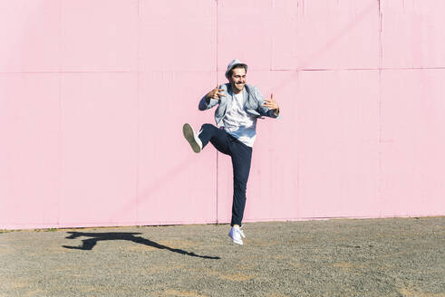 Young man in front of pink construction barrier, jumping in the air - UUF17836