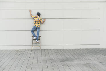 Young man wearing flat hat and aloa shirt, standing on step ladder, touching wall - UUF17878