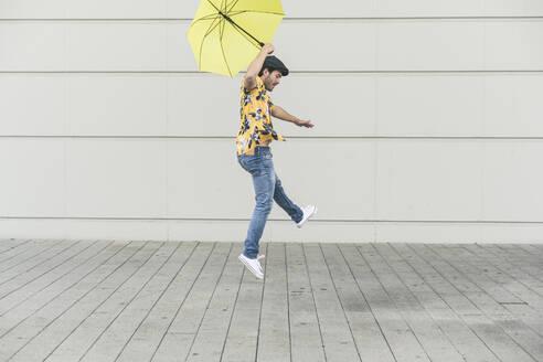Young man with aloha shirt, dancing with yellow umbrella - UUF17881
