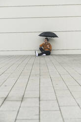 Young man with umbrella, sitting on ground, looking uncertain - UUF17884