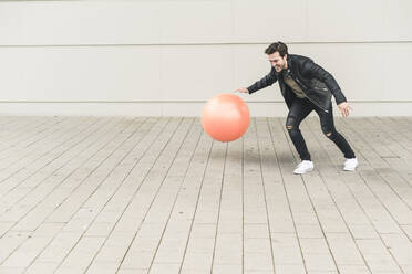 Young man in leather jacket, playing with a gym ball - UUF17893