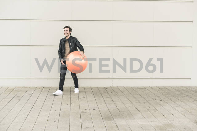 Young man in leather jacket, playing with a gym ball - UUF17899 - Uwe Umstätter/Westend61