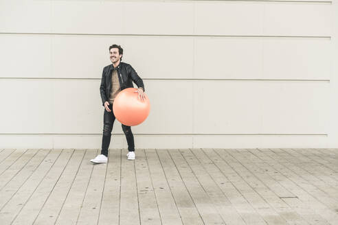 Young man in leather jacket, playing with a gym ball - UUF17899