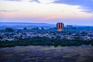Hot air balloon flying over savanna landscape - MINF12513