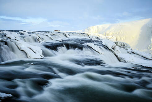 Time lapse view of river flowing over icy rock formations - MINF12564