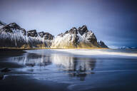 Ocean waves on beach under snowy mountains - MINF12576