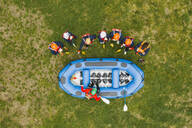 Top view of instructor talking to group of friends at a rafting class - FBAF00709