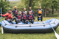 Instructor and group of friends at a rafting class posing in boat - FBAF00718