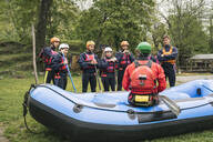 Instructor talking to group of friends at a rafting class - FBAF00721