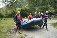 Group of friends preparing for a rafting trip carrying rubber dinghy - FBAF00730
