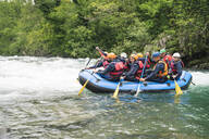 Group of people rafting in rubber dinghy on a river - FBAF00739