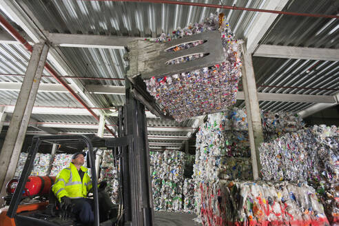 Forklift operator lifting bale of recycled plastic in recycling plant - JUIF01400