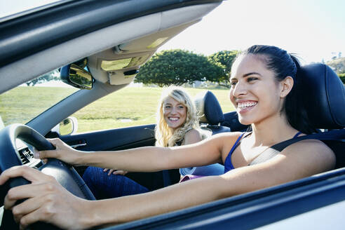 Excited women driving convertible on road trip - BLEF07060