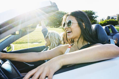 Excited women driving convertible on road trip - BLEF07063