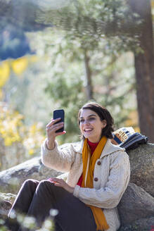 Mixed race hiker taking cell phone selfie in forest - BLEF07168