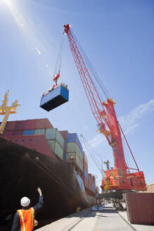 Worker guiding crane unloading container ship at commercial dock - JUIF01437
