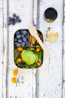 Lunchbox with salad, avocado and yellow tomato, cracker, blueberry and salad dressing, from above - LVF08099
