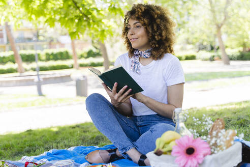 Relaxed woman with book having a picnic in park - FMOF00691