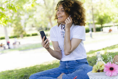 Happy woman with cell phone and earphones having a picnic in park - FMOF00697