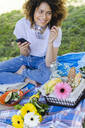 Relaxed woman with cell phone and earphones having a picnic in park - FMOF00700