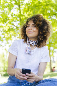 Smiling woman with cell phone and earphones in park - FMOF00703