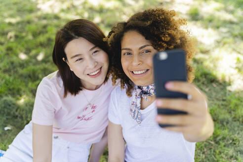 Two happy women taking a selfie in park - FMOF00709