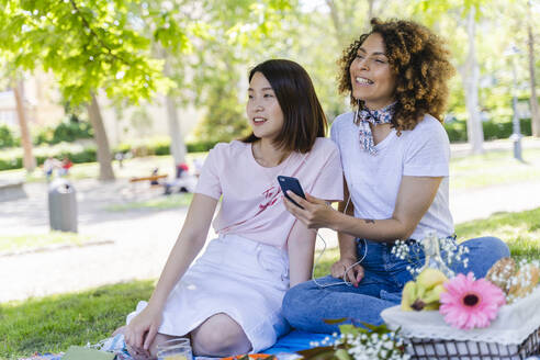 Two women with cell phone and earphones in park - FMOF00712