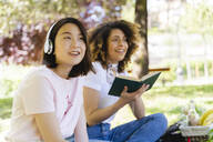 Two women with book and headphones relaxing in park - FMOF00718
