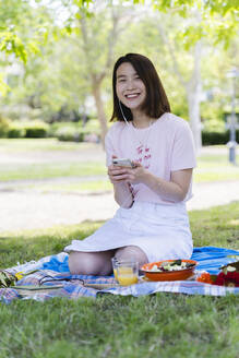 Happy young woman with cell phone and earphones having a picnic in park - FMOF00727