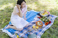 Relaxed woman using cell phone and having a picnic in park - FMOF00730