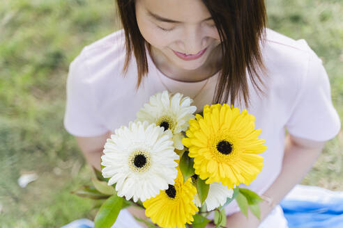 Smiling young woman holding flowers in park - FMOF00733