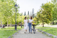 Two women with bicycle walking in park - FMOF00736
