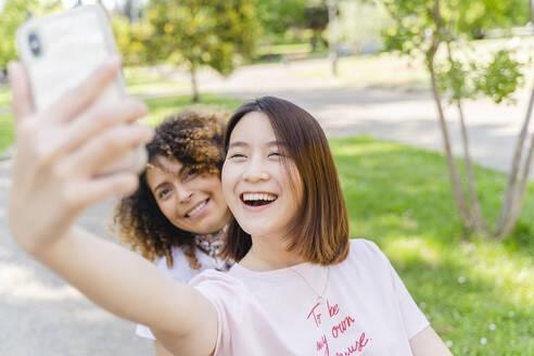 Two happy women taking a selfie in park - FMOF00739