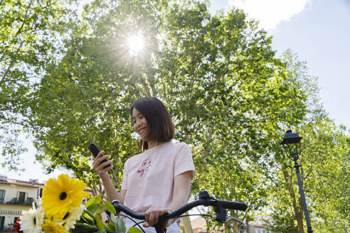 Smiling young woman with cell phone, earphones and bicycle in park - FMOF00742