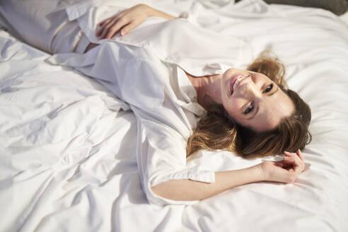 Frau in Schlafanzug auf Bett entspannend, München, Deutschland - PNEF01655