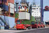 Crane lowering cargo container onto truck at commercial dock - JUIF01452