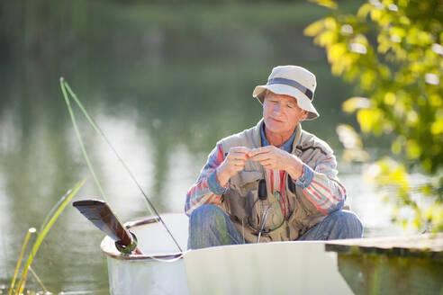 Senior man preparing fishing rod in rowboat on sunny lake - JUIF01467