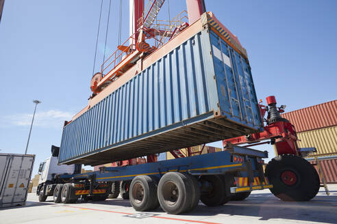 Crane loading cargo container onto lorry at commercial dock - JUIF01473