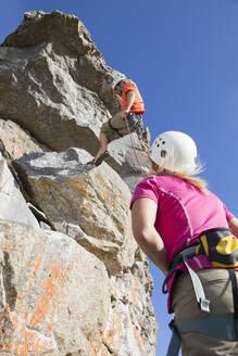 Woman watching male rock climber abseiling down rock face - JUIF01476