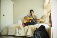 Mixed race boy playing guitar in bedroom - BLEF07209