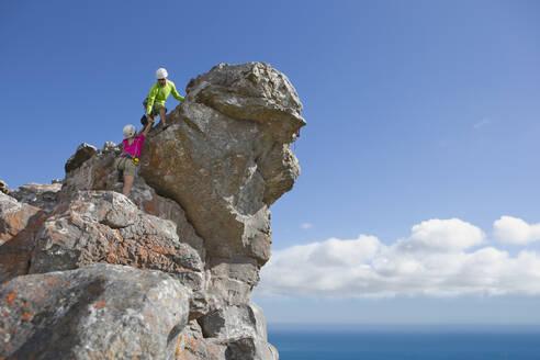 Male rock climber helping woman up rock face - JUIF01513