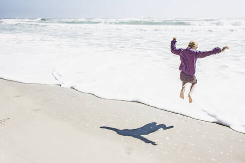 Girl playing in waves on sunny beach - BLEF07389