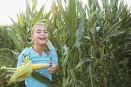 Caucasian girl eating corn in field - BLEF07395