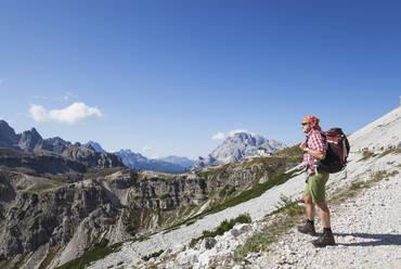 Hiker on hiking trail, Tre Cime di Lavaredo Aera, Nature Park Tre Cime, Unesco World Heritage Natural Site, Sexten Dolomites, Italy - GWF06108
