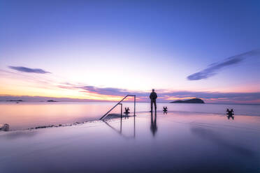 Man standing alone on harbour pier watching the sunset, North Berwick, East Lothian, Scotland - SMAF01255