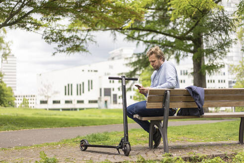 Businessman with E-Scooter sitting on bench in city park using smartphone, Essen, Germany - JOSF03301